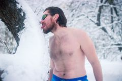 Naked wild man in sunglasses the winter snowy forest Royalty Free Stock Photo