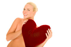 Naked woman with heart-shaped pillow Stock Photos