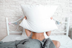 Naked woman hiding behind white pillow in bed Royalty Free Stock Photography