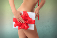 Naked woman holds a gift box with red ribbon next to her hips against colorful textured background. Stock Photography