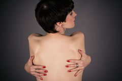 Naked woman hugging a herself tightly Stock Images