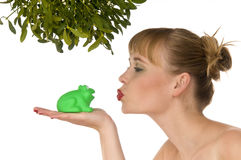 Naked woman kissing a frog under mistletoe. Isolated on white Stock Photo