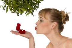 Naked woman kissing a ring under mistletoe. On white background Royalty Free Stock Image