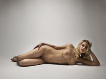 Naked woman laying down on a white background Royalty Free Stock Images