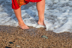 Naked woman legs in sea wave. On the beach Stock Images