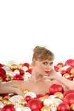 Naked woman lying surrounded by Christmas balls Royalty Free Stock Photography