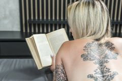 Naked woman reading a book. Naked woman with tattoos, reading a book, lying in bed, view from behind, close-up stock photography