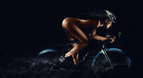 Naked woman riding on a bicycle Stock Images