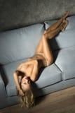 Naked woman on sofa Stock Photos
