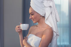 Naked woman with towel on her head and body drinking herbal tea after bath. Royalty Free Stock Image