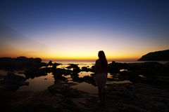 Naked woman watching sunrise. Beautiful young naked woman watching sunrise on Rhodes beach. Greek morning Stock Photo