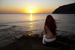 Naked woman watching sunrise. Beautiful young naked woman watching sunrise on Rhodes beach. Greek morning Royalty Free Stock Photo