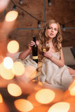 Naked woman wrapped in a blanket with bottle and glass of white wine. Beautiful blonde girl enjoying alcohol. Cozy. Evening of winter holidays Royalty Free Stock Photos