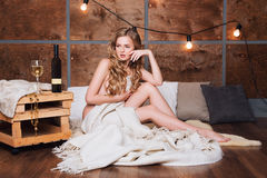 Naked woman wrapped in a blanket with glass of white wine. Beautiful blonde girl enjoying alcohol. Cozy evening, winter. Naked woman wrapped in a blanket with Royalty Free Stock Photography