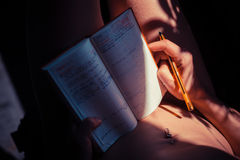Naked woman writing in notebook Royalty Free Stock Images
