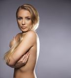 Naked young female covering her breast with hands. Young woman looking at camera while covering her naked body. Copy space right. Beautiful model with bond hair Stock Photo