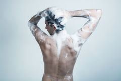 Naked young man covered with soap Stock Image