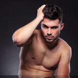 Naked young man fixes his hair Stock Image