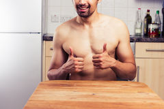 Naked young man in his kitchen giving thumbs up Royalty Free Stock Images