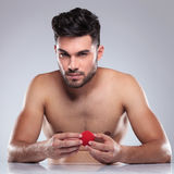 Naked young man holding a red ball Royalty Free Stock Image