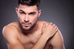 Naked young man holds hand on shoulder Stock Images