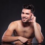 Naked young man leans on hand stock photography