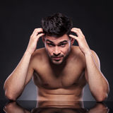 Naked young man scratches head Stock Photos