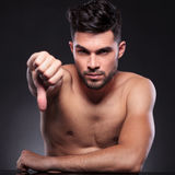Naked young man shows thumb down Royalty Free Stock Photography