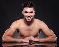Naked young man smiles at desk stock image