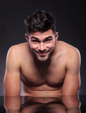 Naked young man smiles at you. Portrait of a naked young man at the desk, looking into the camera with a cute smile on his face. on a black studio backgroud Stock Image
