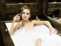 Naked young smiling woman with long hair and straight slim beautiful body lying in white bath tub indoor on wooden Royalty Free Stock Photography