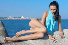 Naked young woman with blue sarong sunbathes at the sea Royalty Free Stock Images