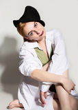 Naked young woman in a man`s white shirt with green tie holding black hat and posing on the floor Royalty Free Stock Image