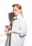 Naked young woman in a man`s white shirt with green tie holding glasess Stock Images