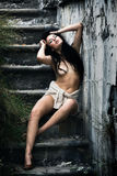 Naked young woman sits on a concrete staircase Royalty Free Stock Photos