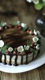 Naken droppandekaka med choklad som dekoreras med jordgubbar, jasminblommor och kaprifolen på den bruna trätabellen Arkivbilder