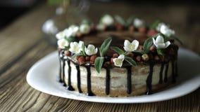 Naken droppandekaka med choklad som dekoreras med jordgubbar, jasminblommor och kaprifolen på den bruna trätabellen Arkivfoto
