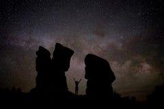 Naken kvinnakontur mot natthimmel med Vintergatan, konstellationer och stjärnor Arkivfoto