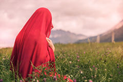 Naken kvinnlig i en röd halsduk i ett fält på solnedgången