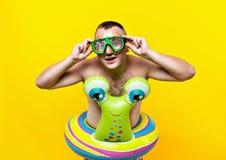 Naken man med en undervattens- maskering som simmar varvar i form av en snigel som ser in i kameran, gul bakgrund Royaltyfria Foton
