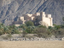 Nakhal Fort, Oman. Off-road in the Sultanate of Oman: Nakhal Fort rises from the wadi bed amongst the date palms against the background of the high jebel. Al Stock Images