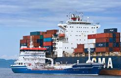 Nakhodka Bay. East (Japan) Sea -  August 2, 2015:  Bunkering tanker Zaliv Nakhodka a large container ship CMA CGM Marlin. Stock Image