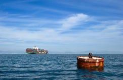 Nakhodka La Russie - 17 septembre 2015 : Vieille balise avec un navire porte-conteneurs chargé à l'ancre à l'arrière-plan Images stock