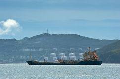 Nakhodka. Russia - August 2, 2015: Tanker Nicholay Shalavin anchor in the roads against the backdrop of an oil terminal company Ro Royalty Free Stock Images