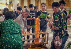 NAKHON PATHOM, TAILANDIA - 25 DE AGOSTO: El budista local prepara velas para encender el incienso para rogar en el templo de Wat  foto de archivo