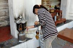Nakhon Pathom, Tailandia: Palillo del incienso de la iluminación de la mujer Imagen de archivo