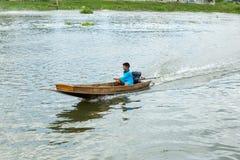 Nakhon Pathom, Tajlandia, Maj/- 26 2018: Chłopiec przejażdżka motorowa łódź, dziecko zręcznie kontroluje motorboat w rzece zdjęcie stock