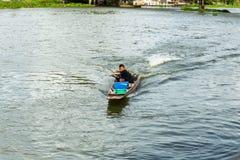 Nakhon Pathom, Tajlandia, Maj/- 26 2018: Chłopiec przejażdżka motorowa łódź, dziecko zręcznie kontroluje motorboat w rzece obrazy stock