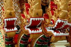 Nakhon, Pathom, Thailand:. Nakhon Pathom, Thailand - December 27, 2005: Carved wooden naga figures with bared teeth at Wat Dai Lom stock photography