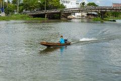 Nakhon Pathom/Thailand - Maj 26 2018: Pojkedrev ett motoriskt fartyg, barn kontrollerar skillfully en motorbåt i floden royaltyfri foto